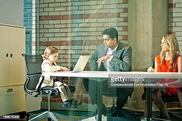 Boy (3-5) chairing business meeting