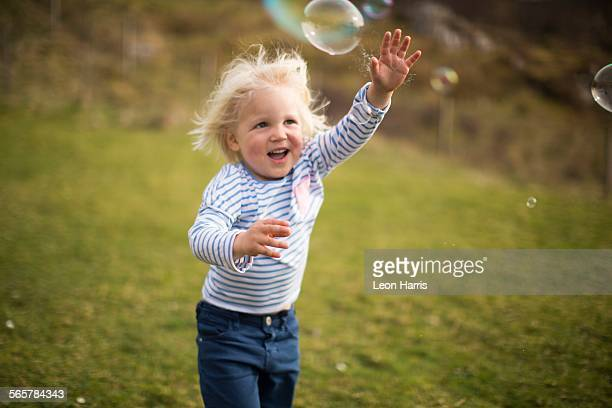 Boy chasing bubble, smiling