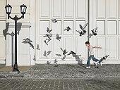 Boy (11-13) chasing pigeons in street