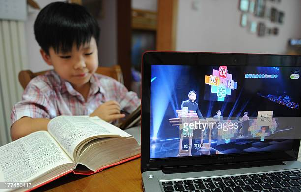 A boy checks a dictionary as he watches a TV programme called 'hanzi yingxiong' or Chinese characters hero at his home in Beijing on August 23 2013...