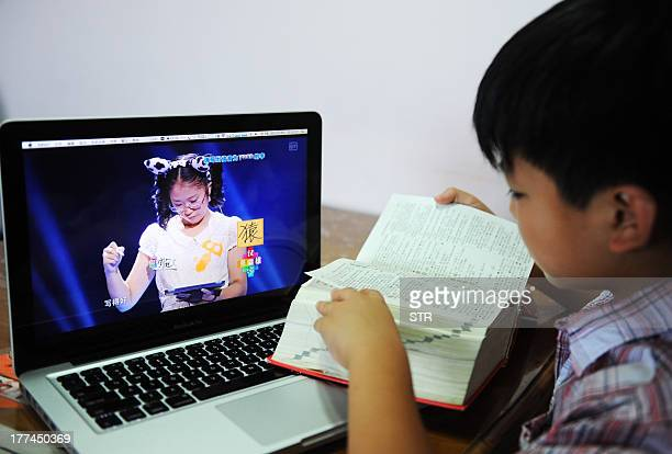 A boy checks a dictionary as he watches a TV programme called 'hanzi yingxiong' Chinese characters hero at his home in Beijing on August 23 2013 AFP...