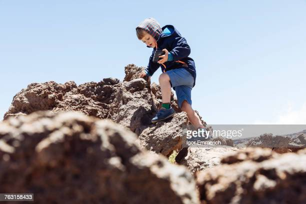 Boy clambering up rocks at Mount Teide, Tenerife, Canary Islands