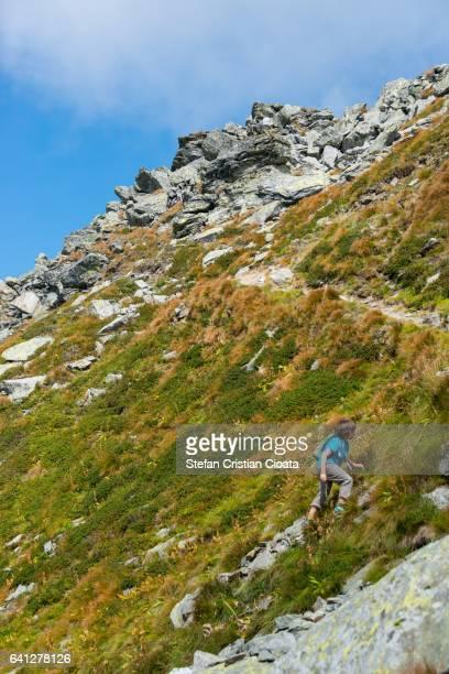 Boy climbing a rocky mountain