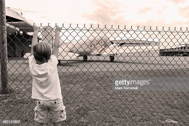 Boy climbing chain link fence around airport