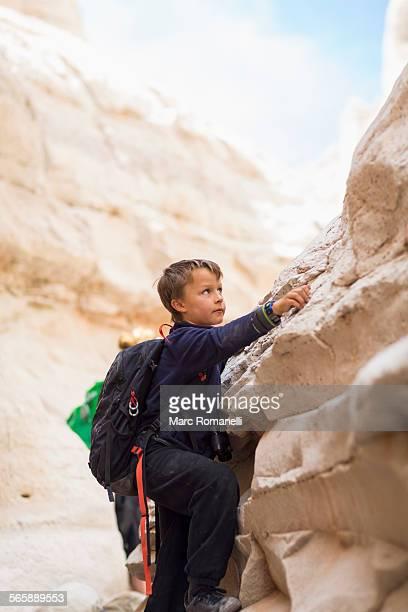 Boy climbing desert rock formations
