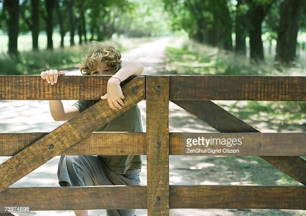 Boy climbing fence