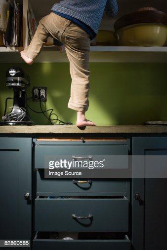 Boy climbing in kitchen