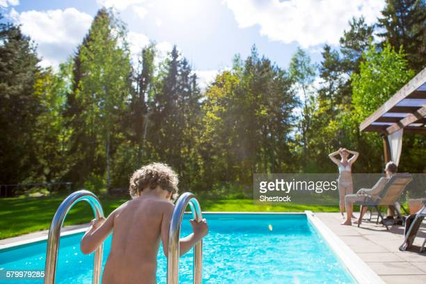 Boy climbing into swimming pool in backyard