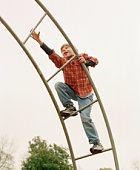 Boy (6-8) climbing jungle jim, reaching, autumn