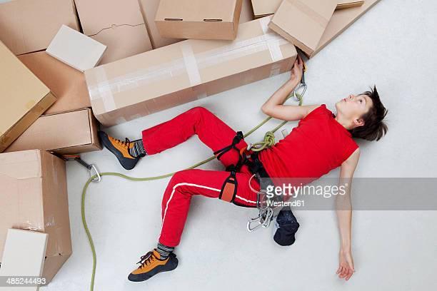 boy climbing mountains made of cardboard boxes