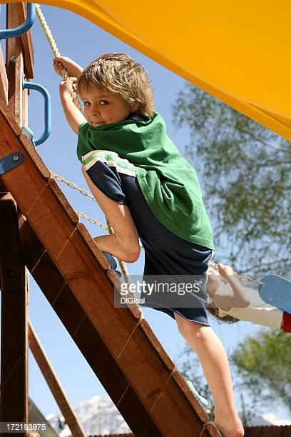 Garçon escalade sur un mur d'escalade
