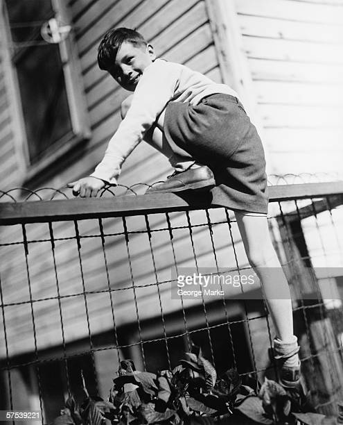 Boy (8-9) climbing on enclosure in front of house, (B&W)