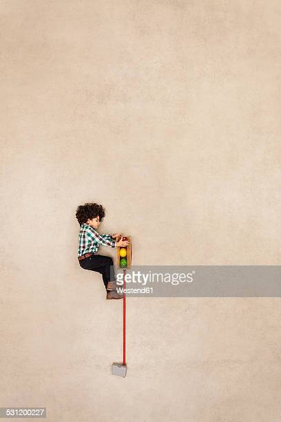Boy climbing on traffic light