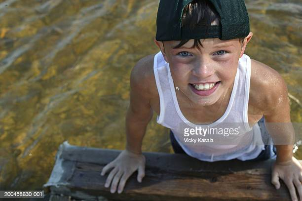 Boy (10-12) climbing out of lake onto dock, portrait, elevated view