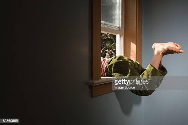 Boy climbing out of window