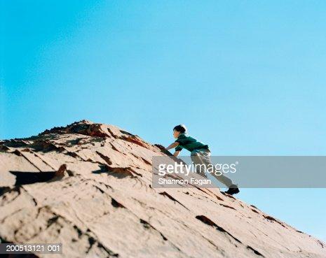 Boy (11-13) climbing rock in desert : Stock Photo