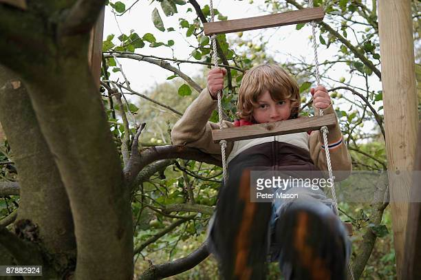 Boy climbing to treehouse