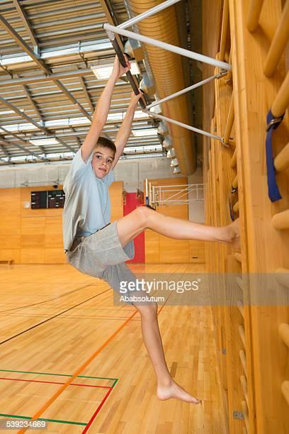 Boy Climbing/Exercising on Wall Bars in School Gymnasium, Europe