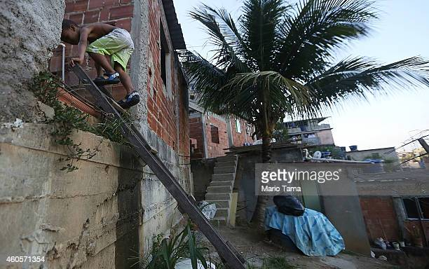 A boy climbs a ladder to his family's residence in the Prazeres favela or community on December 16 2014 in Rio de Janeiro Brazil The city is gearing...