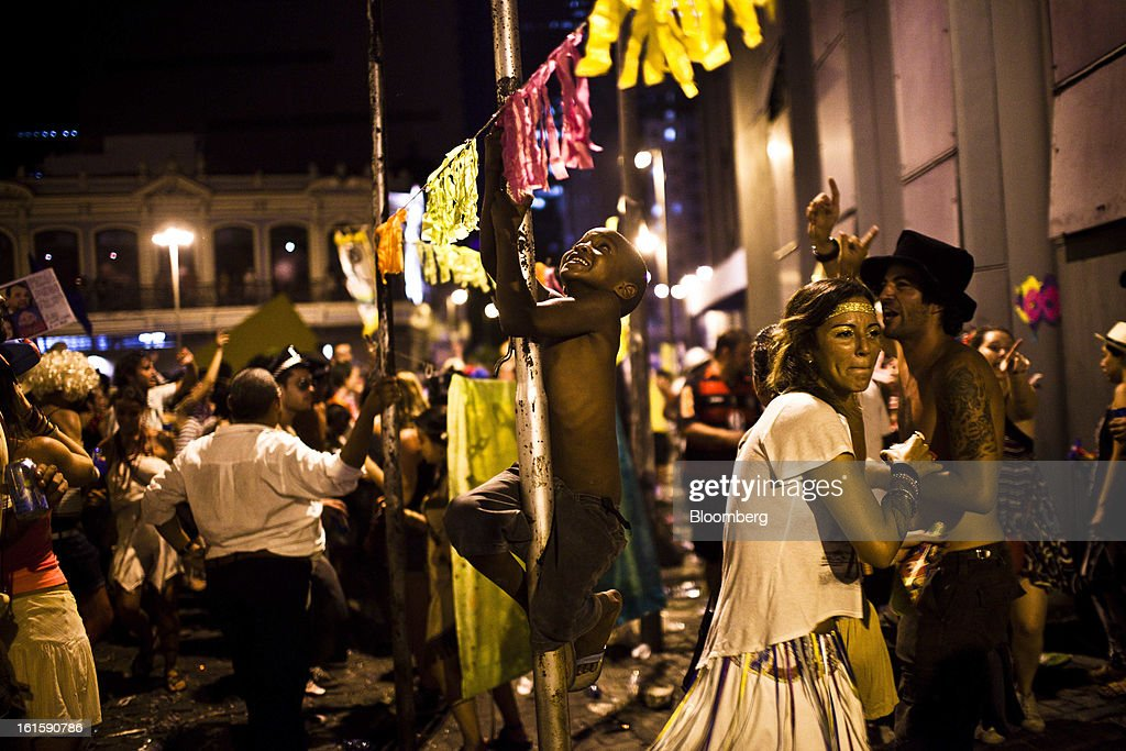 A boy climbs on a light pole at a street party during Carnival celebrations in Rio de Janeiro, Brazil, Monday, Feb. 11, 2013. The festivities, which are expected to attract almost 900,000 visitors, precede the start of Lent, which begins with Ash Wednesday on Feb. 13. Photographer: Dado Galdieri/Bloomberg via Getty Images