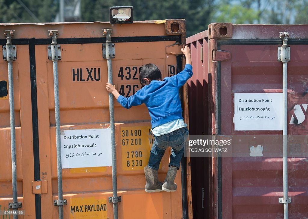 A boy climbs onto a container at a makeshift camp for migrants and refugees near the village of Idomeni not far from the Greek-Macedonian border on May 1, 2016. Some 54,000 people, many of them fleeing the war in Syria, have been stranded on Greek territory since the closure of the migrant route through the Balkans in February. / AFP / TOBIAS