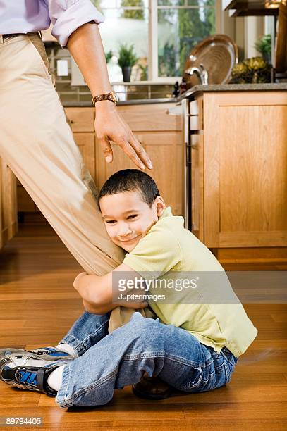 Boy clinging to father