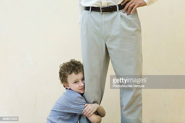 Boy clinging to his father's leg, looking at camera, cropped view
