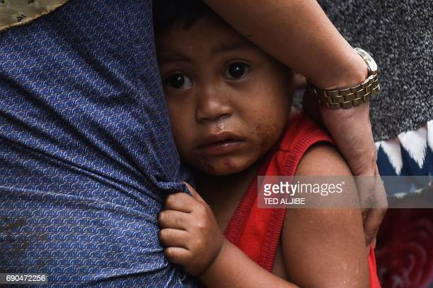 TOPSHOT A boy clutches to his mother after residents where evacuated from their homes on the outskirts of Marawi on the southern island of Mindanao...