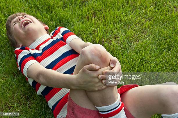 A boy clutching his leg in pain after an accident