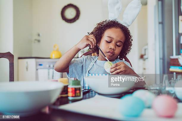 Boy coloring Easter egg at home