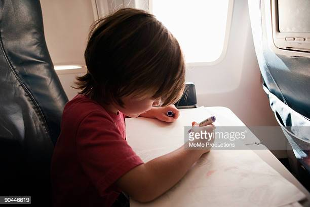 boy (4-5) coloring on airplane