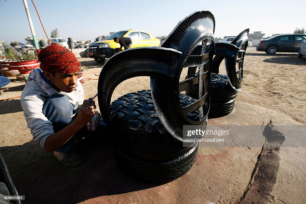 A boy colors the chairs at Abu Haidar's tire repair shop, where he transforms unused tires into furniture, in the Diwaniya village, east of the holy Iraqi city of Najaf, on February 13, 2016. / AFP / HAIDAR HAMDANI
