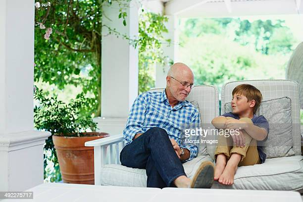 Boy communicating with grandfather at porch