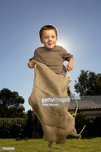 Boy (6-7)  competing in gunnysack race