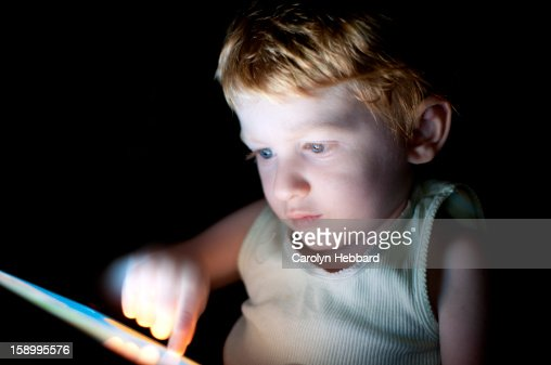 Boy Concentrating on Using Tablet : Stock Photo