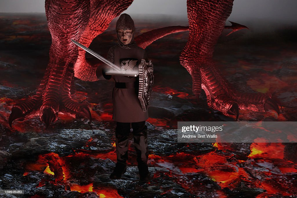 Boy conjures sword from computer to fight dragon : Stock Photo