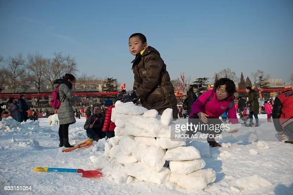 A boy constructs an igloo with snow at an amusement fair in a park during the Spring Festival holidays in Beijing on January 31 2017 Millions of...