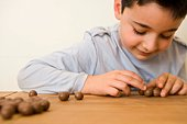 Boy counting chocolate candies on table