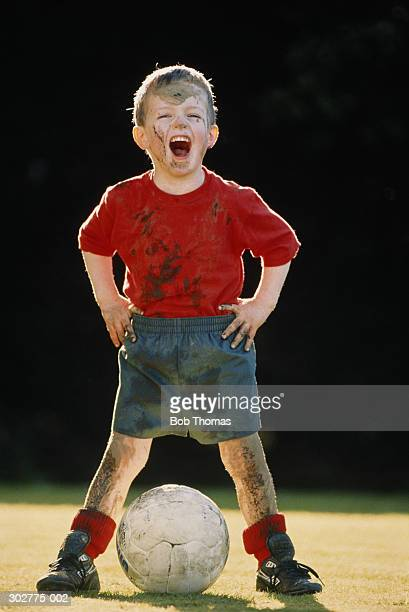 Boy (4-6) covered in mud, standing with football, portrait