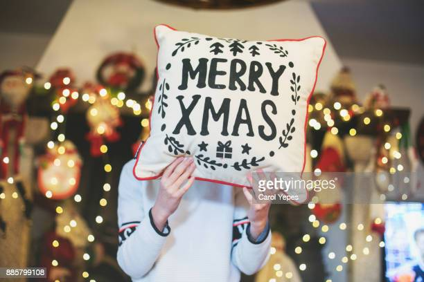 boy covering face with cushion with xmas message