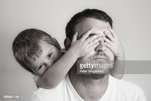 Boy covering fathers eyes : Stock Photo