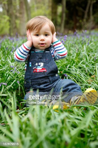 Boy covering his ears in meadow