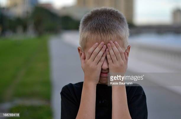 Boy covering his face with hands