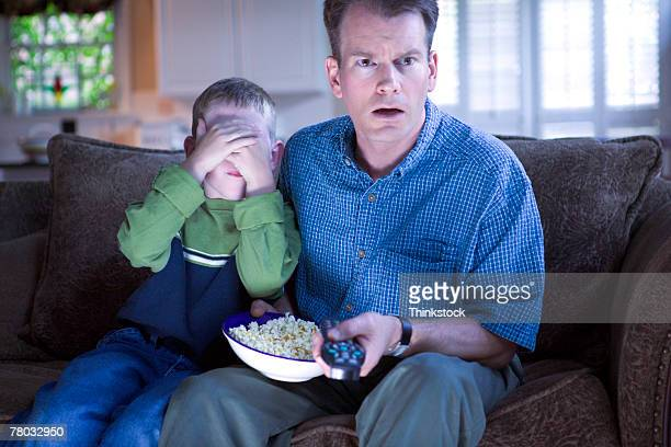 A boy covers his eyes as he and his father watch television