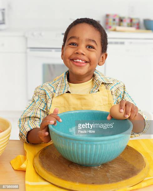 Boy cracking egg into mixing bowl
