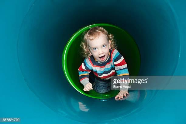 Boy crawling inside plastic tunnel