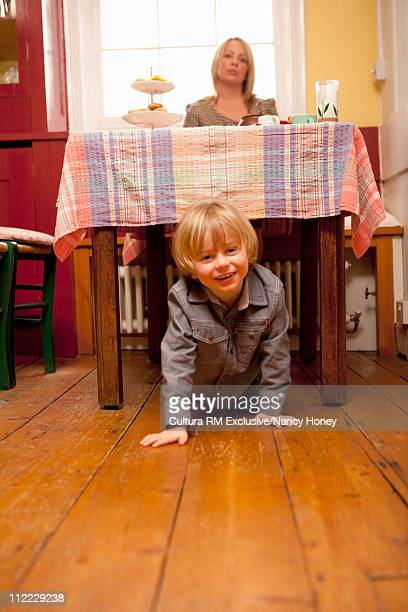 Boy crawling out from under table