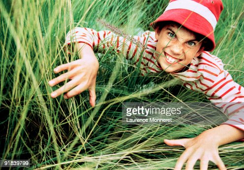 Boy crawling through grass : Stock Photo
