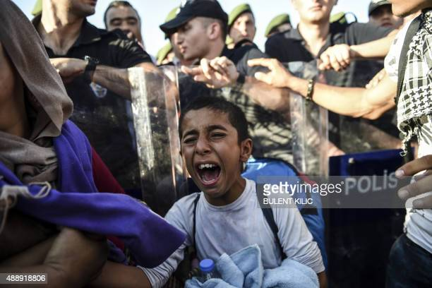 A boy cries as Syrian refugees and migrants push against a police barricade as they march along the highway towards the TurkishGreek border at Edirne...