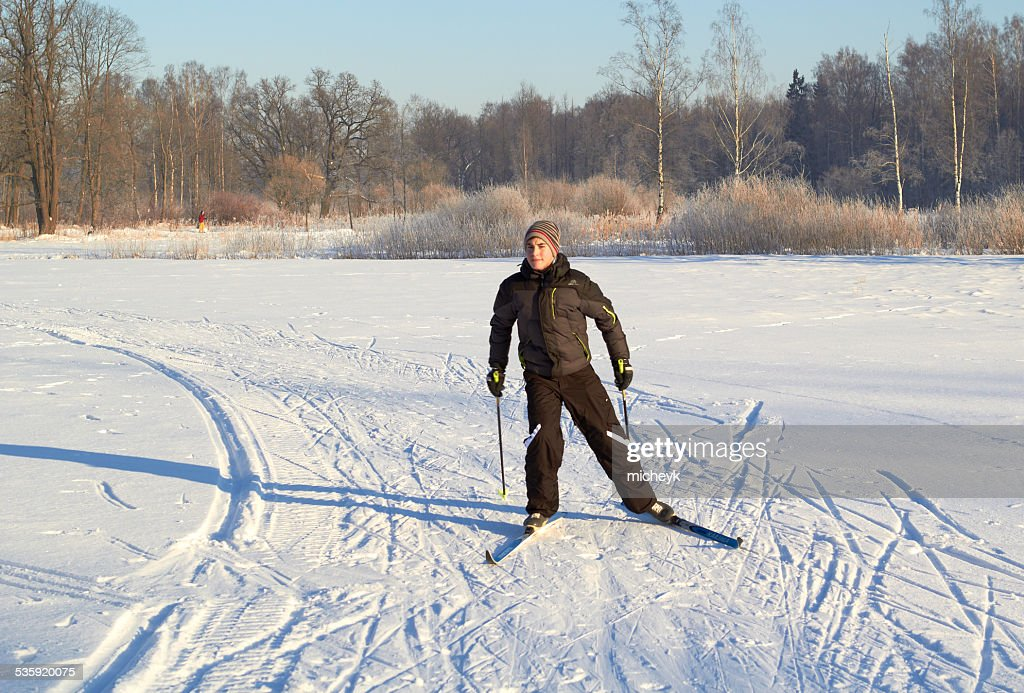 Boy cross country skiing at sunny winter day : Stock Photo